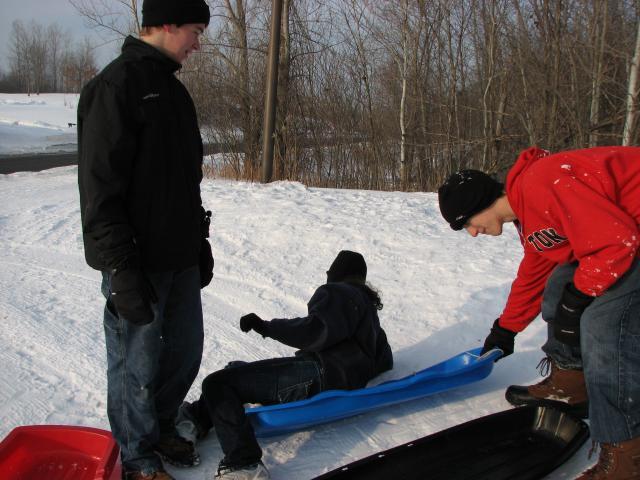 Matt dumps Chelsea out of a sled while Ben laughs.